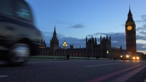 Traffic-passes-in-front-of-Big-Ben-and-Houses-Of-Parliament-in-London-England-at-night-1