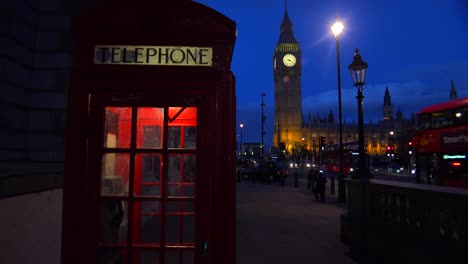 An-iconic-red-telephone-booth-in-front-of-Big-Ben-and-Houses-Of-Parliament-in-London-England-at-night