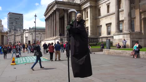 A-street-performer-plays-the-grim-reaper-at-Trafalgar-Square-London-