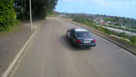An-aerial-shot-over-a-police-car-traveling-on-a-road
