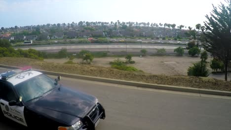 A-slow-motion-aerial-shot-over-a-police-car-traveling-on-a-road