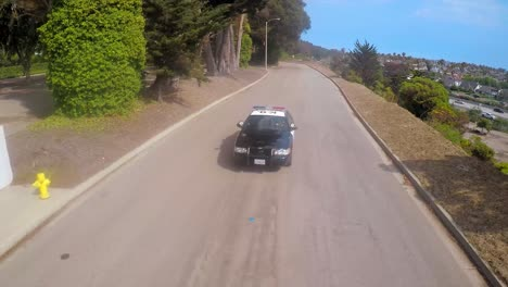 A-slow-motion-aerial-shot-over-a-police-car-traveling-on-a-road-1