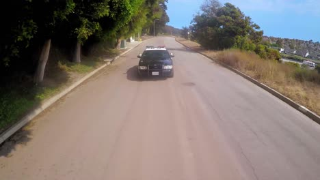 A-slow-motion-aerial-shot-over-a-police-car-traveling-on-a-road-2