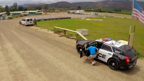 Vista-Aérea-view-above-a-K9-dog-in-training-in-a-mock-shootout-between-Policía-and-criminals