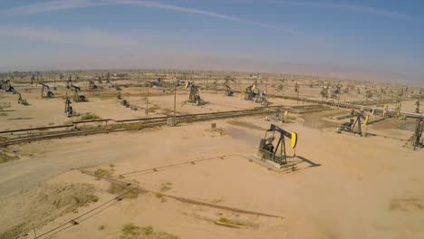 Increíble-Toma-Aérea-Sobre-Vastos-Campos-Petroleros-Y-Torres-De-Perforación-Cerca-De-Bakersfield-California