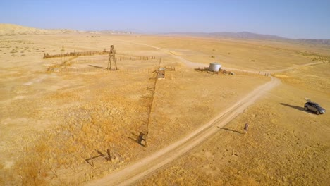 Una-Antena-Sobre-Un-Hombre-Que-Caminaba-Hacia-Su-Automóvil-Cerca-De-Un-Rancho-Abandonado-En-El-Desierto-De-La-Llanura-Del-Carrizo-