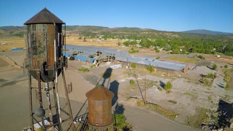 An-aerial-shot-over-an-abandoned-factory-mill-and-water-towers-in-Northern-California