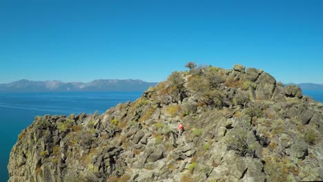 An-aerial-shot-over-a-hiker-on-a-mountaintop-in-Lake-Tahoe-Nevada