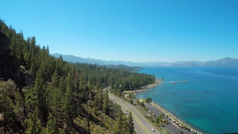 An-aerial-shot-over-a-highway-running-along-the-shoreline-of-Lake-Tahoe