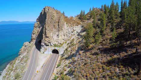 An-aerial-shot-over-a-highway-running-through-a-tunnel-along-the-shoreline-of-Lake-Tahoe-1