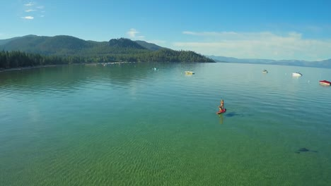 An-aerial-shot-of-a-woman-and-her-dog-paddle-boarding-on-Lake-Tahoe