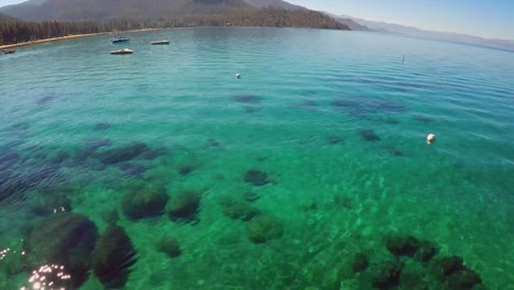 An-aerial-shot-over-a-paddle-boarder-rowing-on-Lake-Tahoe
