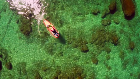 An-aerial-shot-looking-straight-down-over-a-paddle-boarder-rowing-on-Lake-Tahoe-1