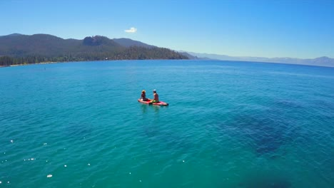 An-aerial-shot-of-a-woman-and-man-sitting-on-a-paddle-board-on-Lake-Tahoe
