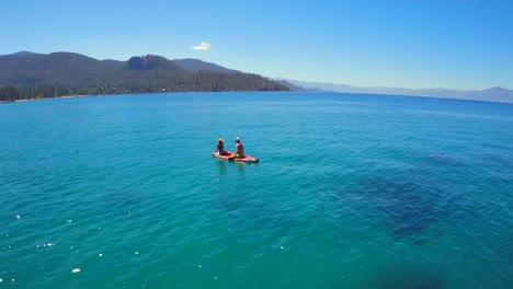 Una-Toma-Aérea-De-Una-Mujer-Y-Un-Hombre-Sentados-En-Una-Tabla-De-Remo-En-El-Lago-Tahoe-