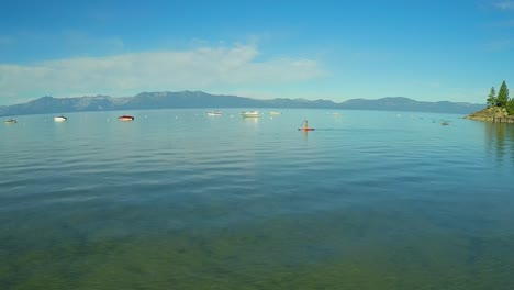 An-aerial-shot-of-a-woman-and-her-dog-paddle-boarding-on-Lake-Tahoe-2