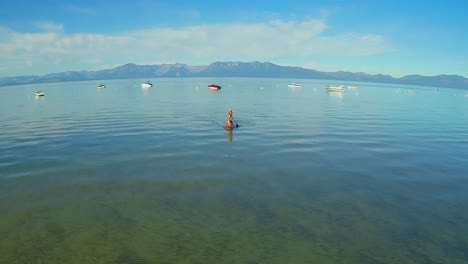 An-aerial-shot-of-a-woman-and-her-dog-paddle-boarding-on-Lake-Tahoe-3