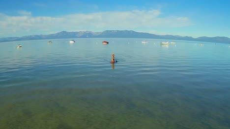 Una-Toma-Aérea-De-Una-Mujer-Y-Su-Perro-Remando-En-El-Lago-Tahoe-3