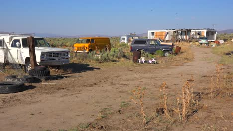 An-abandoned-mobile-home-in-the-desert-is-surrounded-by-old-trucks-and-cars-and-trash