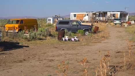 An-abandoned-mobile-home-in-the-desert-is-surrounded-by-old-trucks-and-cars-and-trash-1