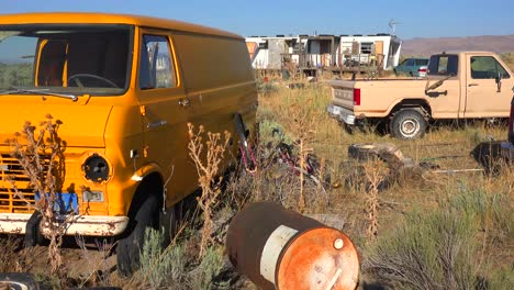 An-abandoned-mobile-home-in-the-desert-is-surrounded-by-old-trucks-and-cars-and-trash-2