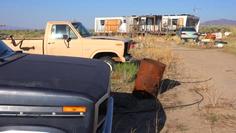 An-abandoned-mobile-home-in-the-desert-is-surrounded-by-old-trucks-and-cars-and-trash-3