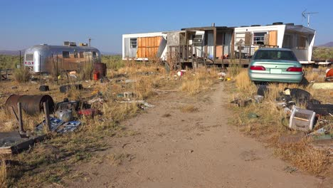 An-abandoned-mobile-home-in-the-desert-is-surrounded-by-old-trucks-and-cars-and-trash-4