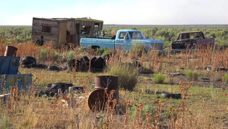 An-abandoned-mobile-home-in-the-desert-is-surrounded-by-old-trucks-and-cars-and-trash-5
