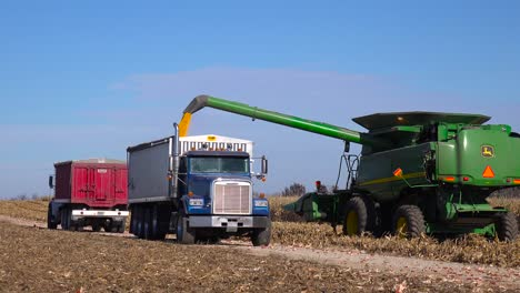 A-harvester-loads-grain-into-a-truck-on-a-rural-farm-in-America