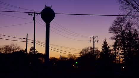 A-rural-water-tank-above-a-small-town-in-dusk-glow