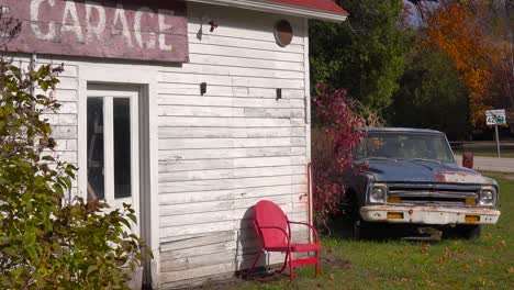 An-attractive-old-weathered-garage-along-a-rural-road-in-America-with-an-abandoned-pickup-truck