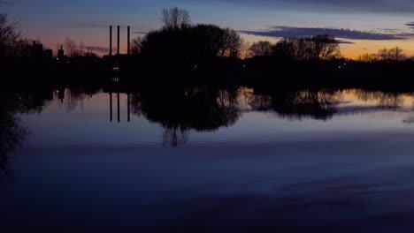 Profundo-Anochecer-En-Un-Hermoso-Lago-Que-Refleja-Las-Chimeneas-De-La-Industria-Y-La-Contaminación-Distante