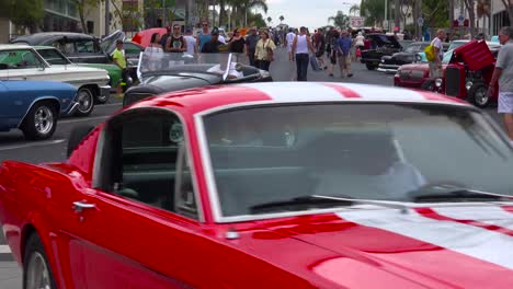 People-wander-on-the-streets-of-a-small-town-looking-at-classic-cars-on-display