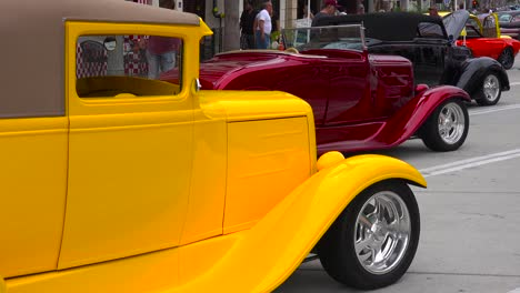 People-wander-on-the-streets-of-a-small-town-looking-at-classic-cars-on-display-1