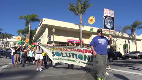 Global-warming-advocates-march-holding-signs-through-an-urban-area