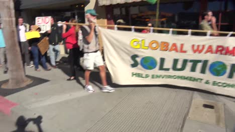 Global-warming-advocates-march-holding-signs-through-an-urban-area-1
