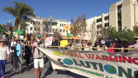 Global-warming-advocates-march-holding-signs-through-an-urban-area-2