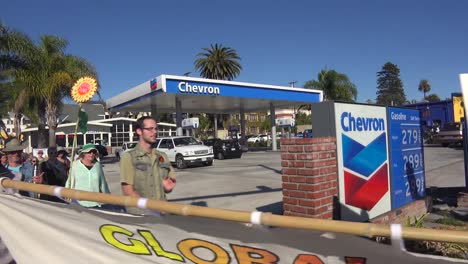 Global-warming-advocates-march-holding-signs-through-an-urban-area-and-past-a-gas-station