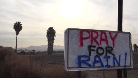 A-sign-says-Pray-For-Rain-along-a-California-highway-during-a-time-of-drought
