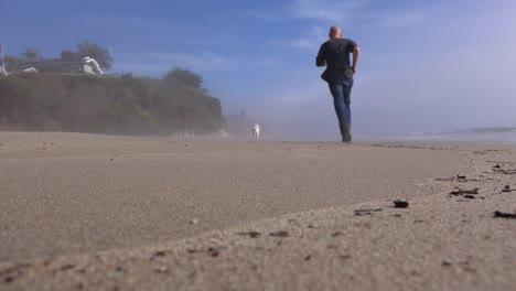 A-man-and-a-dog-jog-on-a-beach