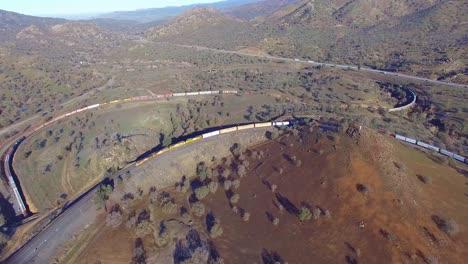 Un-Tren-De-Carga-Recorre-El-Extraordinario-Bucle-De-Tehachapi-En-El-Desierto-De-California-Haciendo-Un-Círculo-Completo-A-Su-Alrededor