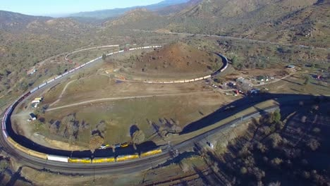 An-aerial-over-a-freight-train-travels-the-remarkable-Tehachapi-Loop-in-California-s-desert-making-a-full-circle-around-itself