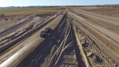 Dramatic-aerial-over-trucks-moving-along-a-highway-under-construction-1
