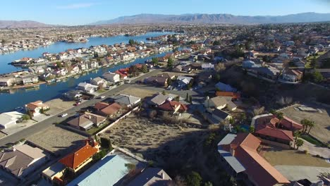 Aerial-over-a-suburban-neighborhood-in-the-desert-with-an-artificial-lake-distant
