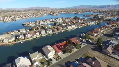 Aerial-over-a-suburban-neighborhood-in-the-desert-with-an-artificial-lake-distant-1
