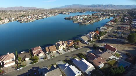 Aerial-over-a-suburban-neighborhood-in-the-desert-with-an-artificial-lake-distant-2