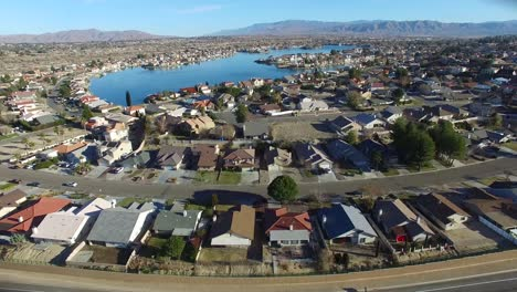Aerial-over-a-suburban-neighborhood-in-the-desert-with-an-artificial-lake-distant-3