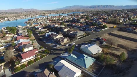 Aerial-over-a-suburban-neighborhood-in-the-desert-with-an-artificial-lake-distant-4