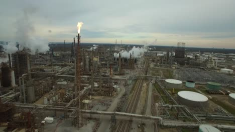 Excellent-aerial-over-huge-industrial-oil-refinery-with-gas-torch-burning