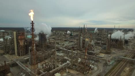 Excellent-aerial-over-huge-industrial-oil-refinery-with-gas-torch-burning-1